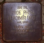 Pamětní destička zasazená v chodníku dnešní Grohovy ulice.