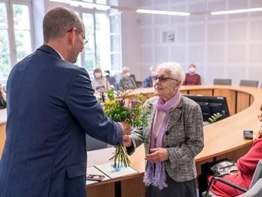 Německý velvyslanec Dr. Christoph Israng předává ocenění a květinu paní Kitty Galdové.