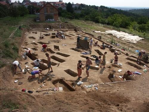 Starší pohled na velký archeologický výzkum centrálního velkomoravského pohřebiště s dosud 601 prošetřenými bohanými hroby. Lze očekávat, že pohřebiště bude jednou z největších dobových nekropolí z 9.-pol. 10. století. Studenti preparují jednotlivé hroby.