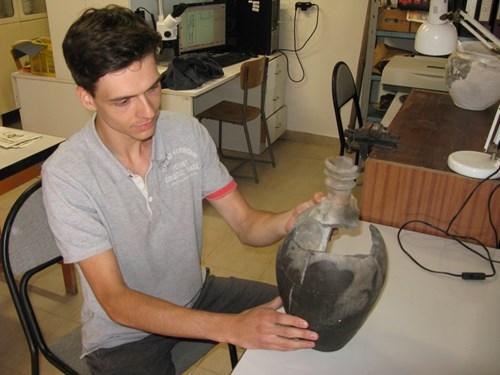 Posluchač Niklas Külzer slepuje a rekonstruuje keramickou láhev.