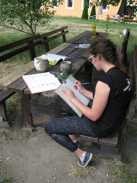 Posluchačka  Silvie Šmardová kreslí keramické nádoby z centrálního pohřebiště.  Foto: B.Klíma